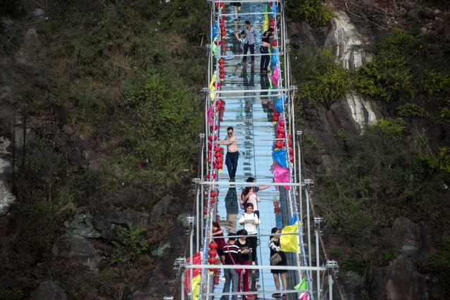 Chinese tourists walk across a glass-bottomed suspension bridge in the Shinuizhai mountains in Pingjang county, Hunan province some 150 kilometers from Changsha on October 8, 2015. The bridge, originally a wooden walkway spanning some 300 meters across the 180-meter deep valley, reopened two weeks ago following renovations as a glass-bottomed tourist attraction. (Photo by Johannes Eisele/AFP Photo)