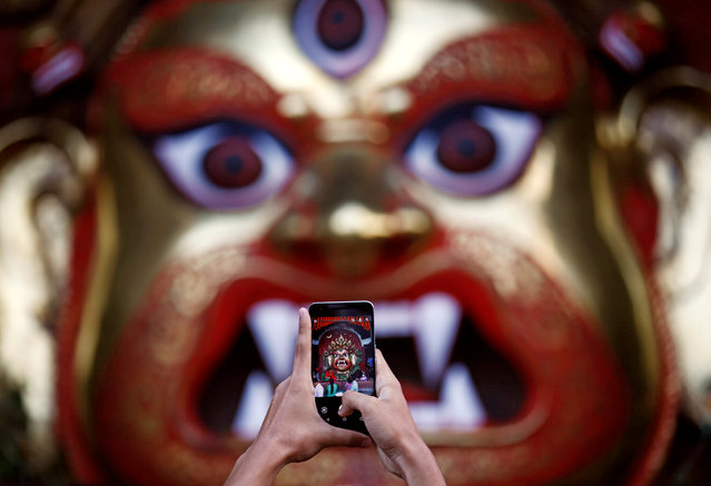 "A devotee takes a picture of an idol of ""Swet Bhairab"" during the Indra Jatra festival in Kathmandu, Nepal, September 13, 2016. (Photo by Navesh Chitrakar/Reuters)"