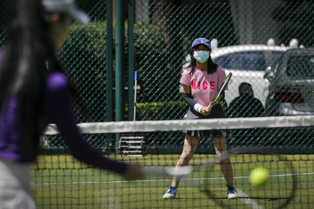 A woman wearing a face mask to help curb the spread of the coronavirus plays tennis with her friend at a court in Beijing, Monday, August 24, 2020. China has gone eight days without reporting a new local case of COVID-19, with the Beijing International Film Festival among public events that are returning. (Photo by Andy Wong/AP Photo)