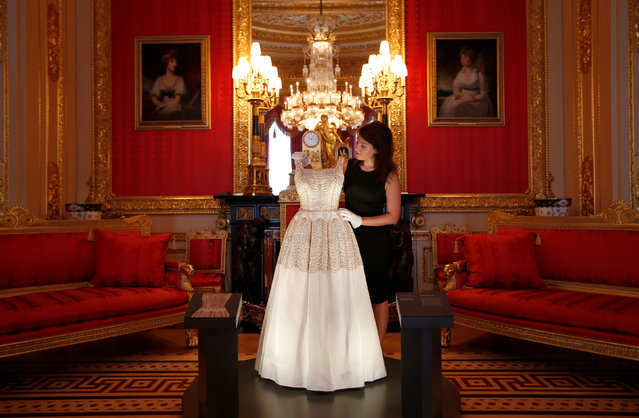 A member of staff of the Royal Collection poses with a dress worn by Britain's Queen Elizabeth, in the Crimson Drawing Room at Windsor Castle in Windsor, Britain September 15, 2016. The exhibition Fashioning a Reign: 90 Years of Style from The Queen's Wardrobe, will show at the castle from September 17, 2016 to January 8, 2017. (Photo by Peter Nicholls/Reuters)