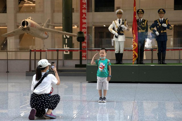 A child salutes for a photo near statues of Chinese military honor guards at the military museum in Beijing on Thursday, September 3, 2020. Seventy-five years after Japan's surrender in World War II, and 30 years after its economic bubble popped, the emergence of a 21st century Asian power is shaking up the status quo. As Japan did, China is butting heads with the established Western powers, which increasingly see its growing economic and military prowess as a threat. (Photo by Ng Han Guan/AP Photo)