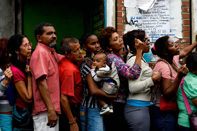 People queue up to buy food and basic household items in a supermarket at the Petare neighborhood in Caracas on July 16, 2016. The Venezuelan military began overseeing food distribution at ports, airports and businesses Tuesday as part of a plan by President Nicolas Maduro to alleviate acute shortages plaguing the country. (Photo by Federico Parra/AFP Photo)