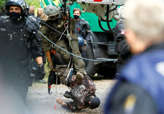 A police special forces officer brings down a protester staging a blockade as the police and forest workers clear a camp at the Dannenrod forest during a protest of environmentalists against the extension of the highway Autobahn 49, in Dannenrod, Germany on September 16, 2020. (Photo by Kai Pfaffenbach/Reuters)