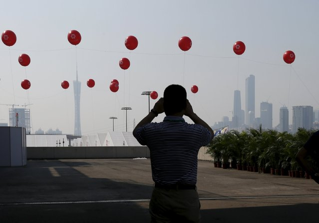 A man takes a photo of the skyline with balloons being displayed outside the venue of the China Import and Export Fair, also known as Canton Fair, in the southern Chinese city of Guangzhou October 15, 2015. (Photo by Bobby Yip/Reuters)