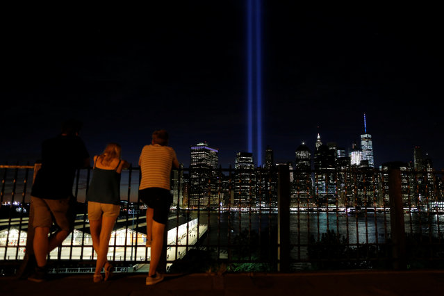 People look on as the Tribute in Light shines on the 15th anniversary of the 9/11 attacks in Manhattan, New York, U.S., September 11, 2016. (Photo by Andrew Kelly/Reuters)