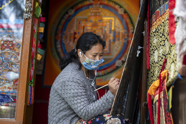 A woman wearing a mask to protect herself from the coronavirus paints a thangka, a traditional Tibetan Buddhist painting in Dharmsala, India, Tuesday, September 15, 2020. (Photo by Ashwini Bhatia/AP Photo)