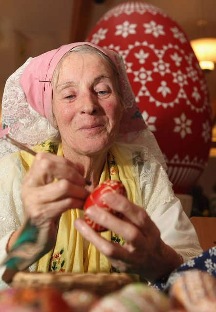 Sorb egg painter Sigrid Bolduan paints an easter egg at the annual Easter egg market on March 16, 2013 in Schleife, Germany. Easter is a particularly important time of year for Sorbs, a Slavic minority in eastern Germany, and the period includes the tradition of painting Easter eggs that include visual elements intended to ward off evil. Many Sorbs still speak Sorbian, a language closely related to Polish and Czech.  (Photo by Adam Berry)