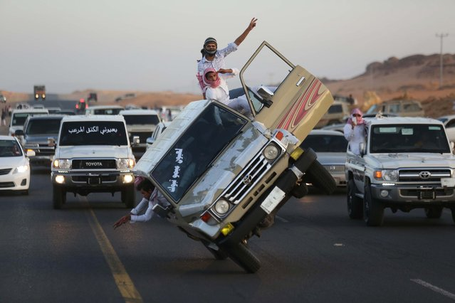 "Saudi youths demonstrate a stunt known as ""sidewall skiing"" (driving on two wheels) in the northern city of Tabuk, in Saudi Arabia December 3, 2014. (Photo by Mohamed Al Hwaity/Reuters)"