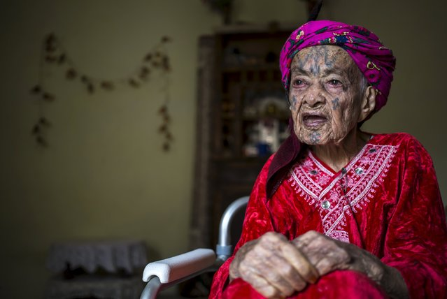 """Fatma Tarnouni, 106, a berber woman from the Chaouia region, who has facial tattoos, sits inside her house in Taghit in the Aures Mountain near the eastern city of Batna, Algeria October 8, 2015. Fatma was tattooed aged 10 by a man from the Sahara region. """"It was the rule, it was fashionable too. All the girls were tattooed. To be beautiful, you had to be tattooed, so I did it."""" Some believers have told these Muslim women that by allowing the tattoos they committed a sin according to Islam. (Photo by Zohra Bensemra/Reuters)"""