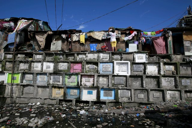 """A woman living atop an """"apartment-style"""" grave hangs out her laundry inside a cemetery in Navotas city, north of Manila October 31, 2015. (Photo by Romeo Ranoco/Reuters)"""