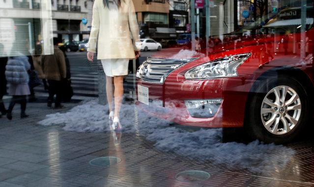 A staff walks near Nissan Motor's Teana sedan as pedestrians and snow are reflected in a window at the company's showroom in Tokyo February 10, 2014. (Photo by Toru Hanai/Reuters)