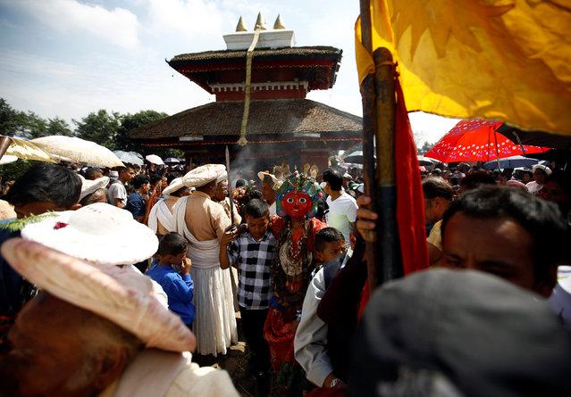 Boys hold a medium (C) dressed as a deity during a trance while celebrating Shikali festival at Khokana village in Lalitpur, Nepal October 7, 2016. (Photo by Navesh Chitrakar/Reuters)