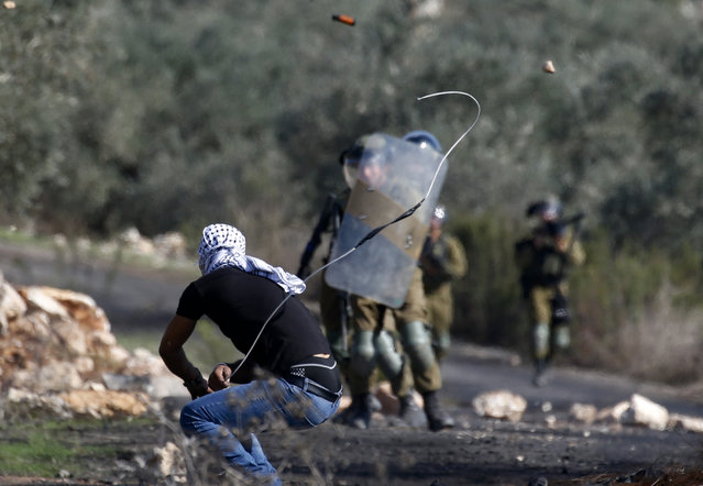 A Palestinian demonstrator uses a slingshot to hurl stones toward Israeli security forces during clashes with them following a weekly demonstration in the occupied West Bank village of Kfar Qaddum, on November 13,  2020. (Photo by Jaafar Ashtiyeh/AFP Photo)