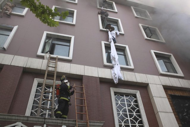 A firefighter holds a ladder as people climb down at the site of a hotel fire in Xiangyang, Hubei province, April 14, 2013. At least 11 people have been confirmed dead and 50 others injured in the fire on Sunday morning, Xinhua News Agency reported. (Photo by Reuters/China Daily)