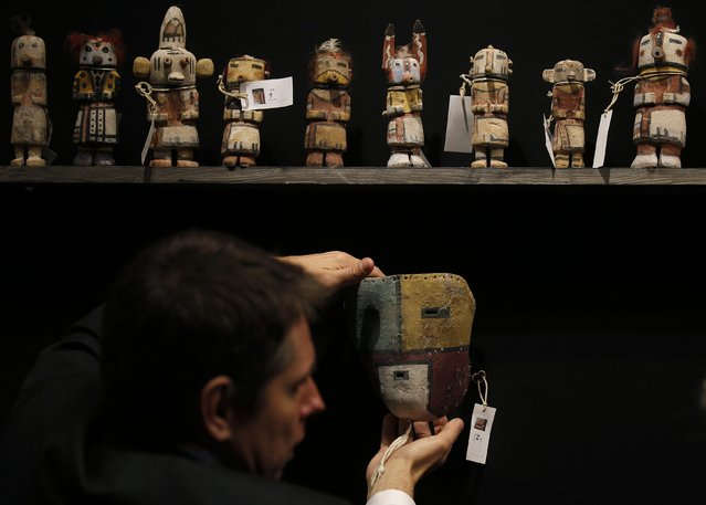 An expert hangs a rare antique Tuma Uyim mask below Kachina dolls made by the Native American Hopi and Zuni tribes displayed at the Drouot auction house in Paris before auction, December 15, 2014. (Photo by Christian Hartmann/Reuters)