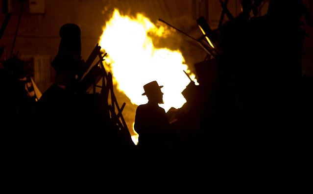 An Ultra-Orthodox Jewish man looks at a bonfire during Lag Ba'Omer celebrations held to commemorate the end of a plague said to have decimated Jews in Roman times, in Bnei Brak, Israel, on April 27, 2013. (Photo by Ariel Schalit/Associated Press)