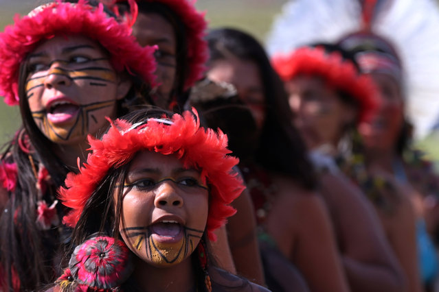 Brazilian Pataxo women take part in a ritual dance during a protest against a proposed constitutional amendment that would put the demarcation of indigenous lands into the hands of the Congress, in front of the Brazil's National Congress, in Brasilia, Brazil, Tuesday, November 10, 2015. A lower house commission has approved the proposal but it must make its way through the Senate, and be signed by President Dilma Rousseff to become law. (Photo by Eraldo Peres/AP Photo)