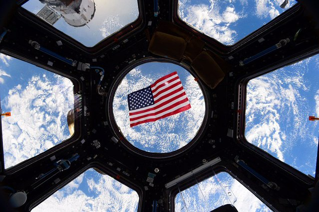 An American flag is framed in the windows of the International Space Station in this undated picture taken by astronaut Kjell Lindgren released on Veteran's Day, November 11, 2015. (Photo by Kjell Lindgren/Reuters/NASA)