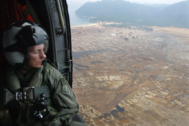 In this January 4, 2005 file photo, Senior Chief Petty Officer James Cash from San Diego, California, surveys damage to Banda Aceh town from the tsunami wave from a United States Naval helicopter flying over the Indonesian province of Aceh. (Photo by Andy Eames/AP Photo)