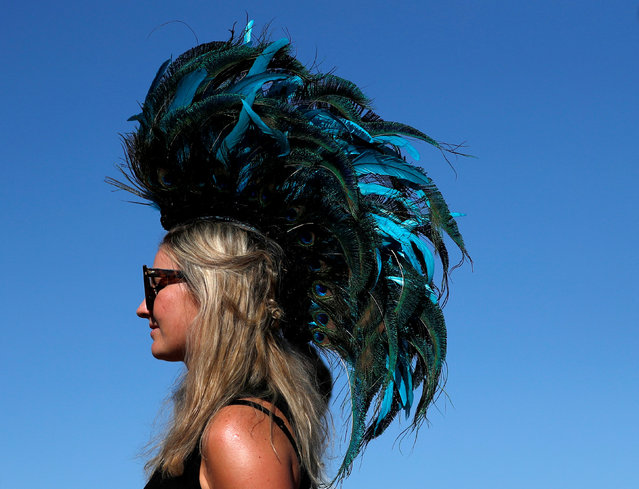 A concertgoer is wearing a feather headpiece at the Coachella Valley Music and Arts Festival in Indio, California, U.S., April 14, 2018. (Photo by Mario Anzuoni/Reuters)