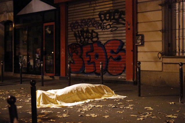 A victim under a blanket lays dead outside the Bataclan theater in Paris, Friday November 13, 2015. (Photo by Jerome Delay/AP Photo)