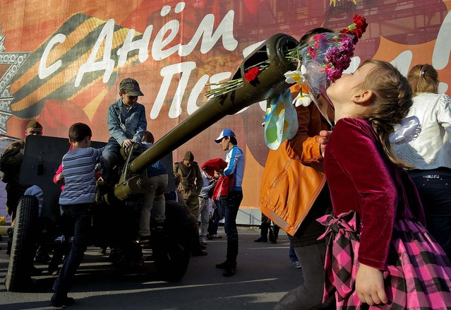 A girl smells the flowers inserted in the barrel of an artillery canon during Victory Day celebrations in St. Petersburg, Russia. (Photo by Dmitry Lovetsky/Associated Press)