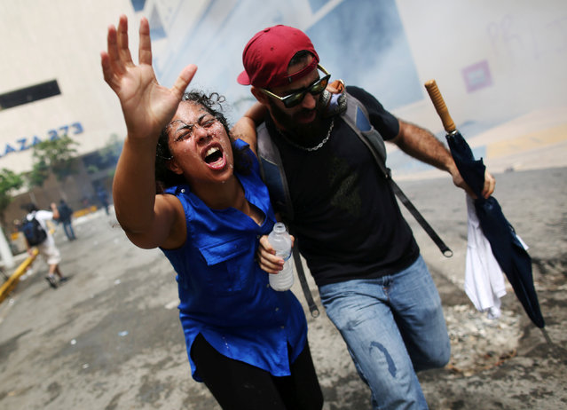 A woman affected by tear gas is assisted during a May Day protest against austerity measures, in San Juan, Puerto Rico May 1, 2018. (Photo by Alvin Baez/Reuters)