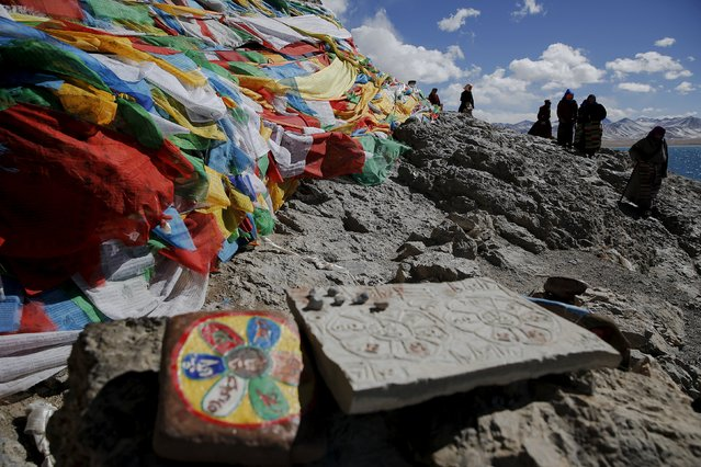 Tibetan people circle around a rock decorated with prayer flags at Namtso lake in the Tibet Autonomous Region, China November 18, 2015. (Photo by Damir Sagolj/Reuters)