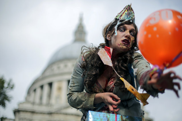 "A woman wearing a costume poses for a photograph as she participates in a ""Zombie Walk"" on World Zombie Day, in central London on October 8, 2016 World Zombie Day is an international annual event that grew from Pittsburgh' s first ever Zombie Walk at Monroeville Mall in 2006 – the setting for Dawn of the Dead. Now, more than 50 cities participate in the event, which in London, is used as an opportunity to raise money for chairty. (Photo by Daniel Leal- Olivas/AFP Photo)"