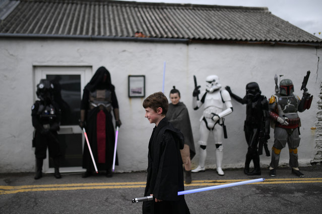 "A boy with a light saber walks past a group of Star Wars fans dressed in costumes during the inaugural ""May The 4th Be With You"" festival in the County Kerry village of Portmagee, Ireland on May 4, 2018. (Photo by Clodagh Kilcoyne/Reuters)"