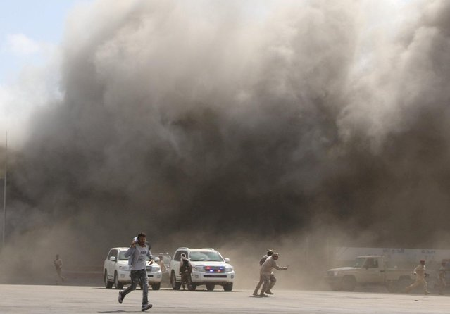 People react as dust rises after explosions hit Aden airport, upon the arrival of the newly-formed Yemeni government in Aden, Yemen on December 30, 2020. (Photo by Fawaz Salman/Reuters)