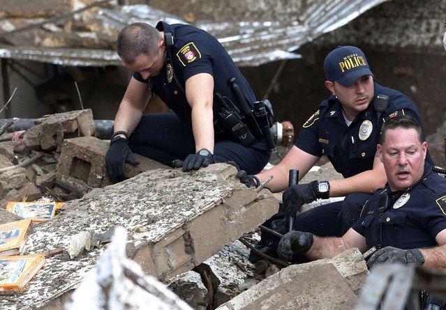 Moore police dig through the rubble of the Plaza Towers Elementary School following a tornado in Moore, Okla., Monday, May 20, 2013. (Photo by Sue Ogrocki/AP Photo)