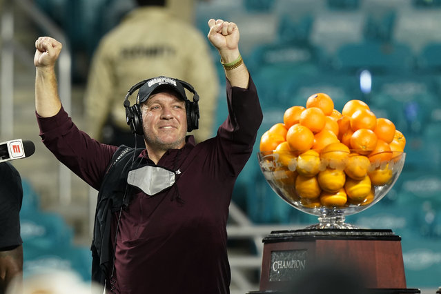 Texas A&M head coach Jumbo Fisher raises his hands during the trophy presentation at the Orange Bowl NCAA college football game, Saturday, January 2, 2021, in Miami Gardens, Fla. Texas A&M defeated North Carolina 41-27. (Photo by Marta Lavandier/AP Photo)