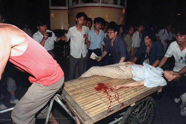 A girl wounded during the clash between the army and students near Tiananmen Square is carried out by a cart, on June 4, 1989. (Photo by Manuel Ceneta/AFP Photo)