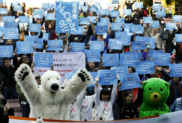 People hold placards demanding climate protection during a protest organised by environment protection groups ahead of the 2015 Paris Climate Conference, known as the COP21 summit, in Tokyo, November 28, 2015.  REUTERS/Thomas Peter