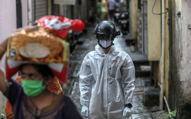 An Indian health worker wearing smart helmet walks after conducting the thermal screening of residents of a slum in Mumbai, India, 14 July 2020. Countries around the world are still taking measures to stem the spread of the SARS-CoV-2 coronavirus which causes the COVID-19 disease and have intensified their research for treatment. (Photo by Divyakant Solanki/EPA/EFE)