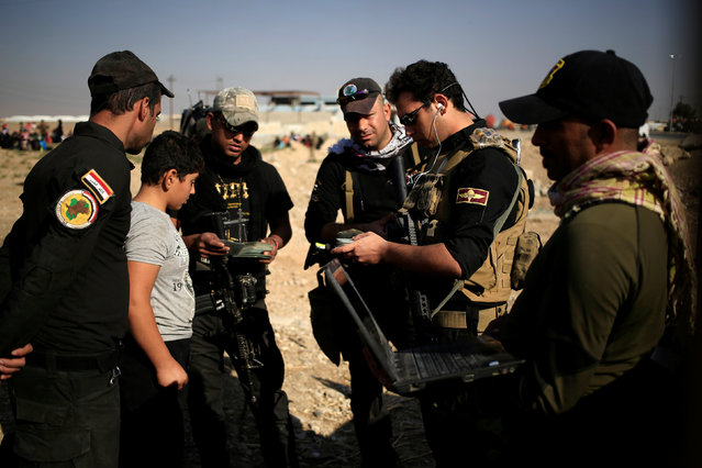 A boy, who just fled the Samah district of eastern Mosul, stands with the Special Forces holding men's identification cards, as they conduct interrogations to ensure the displaced do not belong to the Islamic State group, at the Iraqi Special Forces checkpoint in Kokjali, east of Mosul, Iraq November 5, 2016. (Photo by Zohra Bensemra/Reuters)