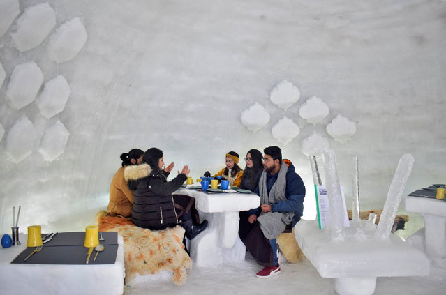 """Tourists drink inside """"Igloo Cafe"""", a cafe prepared with snow and ice, at Gulmarg, a ski resort and one of the main tourist attractions in Kashmir region, January 28, 2021. (Photo by Sanna Irshad Mattoo/Reuters)"""