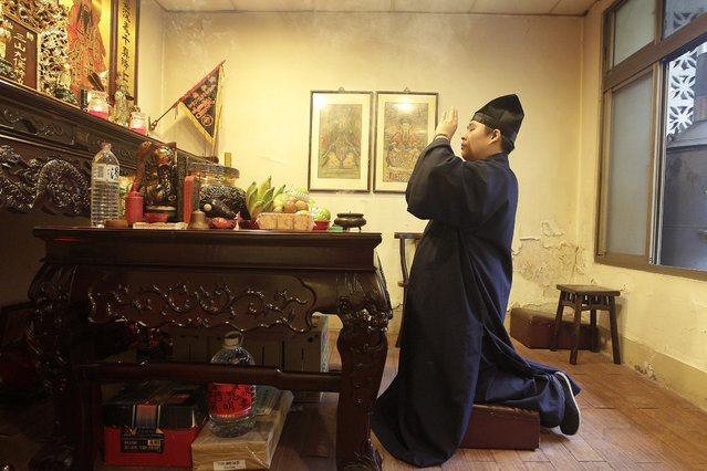 Lu Wei-ming, pirest of the Wei-ming temple, prays while burning incense at the temple in New Taipei city January 8, 2015. (Photo by Pichi Chuang/Reuters)