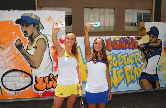 Elina Svitolina of Ukraine and Monica Puig of Puerto Rico take selfies after painting street art with Melbourne graffiti artist Daniel Wenn (unseen) during the ellesse Tennis Performance Apparel Launch on January 17, 2014 in Melbourne, Australia. The new range of tennis performance apparel will be worn by Feliciano Lopez, Elina Svitolina and Monica Puig at the Australian Open.  (Photo by Scott Barbour/Getty Images for ellesse)