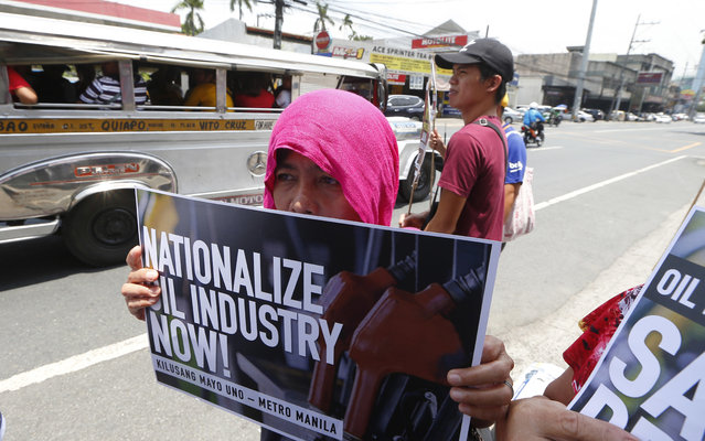 Protesters display placards at passing motorists during a rally outside a filling station to protest another round of oil price increase being anticipated this week Monday, May 21, 2018, in suburban Quezon city northeast of Manila, Philippines. The protesters decried the almost-weekly price increase of gasoline and other oil products which they claimed will also trigger price adjustments on goods and services. (Photo by Bullit Marquez/AP Photo)
