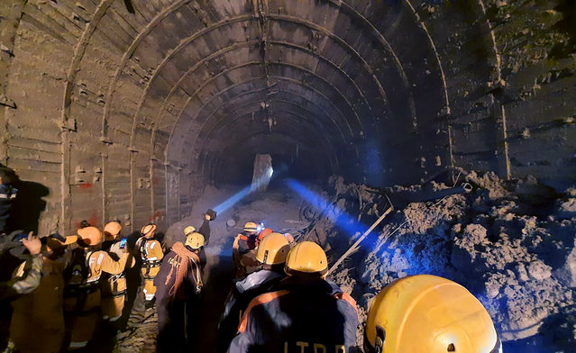 This photograph provided by Indo Tibetan Border Police (ITBP) shows ITBP personnel use torches to gain access inside a tunnel to rescue more than three dozen power plant workers trapped inside it after part of a Himalayan glacier broke off Sunday and sent a wall of water and debris rushing down the mountain in Tapovan area of the northern state of Uttarakhand, India, Tuesday, February 9, 2021. Hundreds of rescue workers were scouring muck-filled ravines and valleys in northern India on Tuesday looking for survivors after part of a Himalayan glacier broke off, unleashing a devastating flood that has left at least 31 people dead and 165 missing. (Photo by Indo Tibetan Border Police via AP Photo)