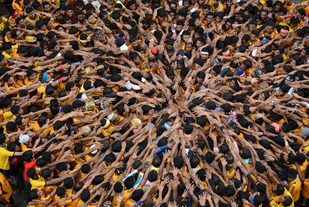"""""""Hands of Unity"""". Young people press together to build a human pyramid during Janmashtami, the birth anniversary of the Hindu god Krishna, in Mumbai, India. The object of the game, called Dahi Handi, is to catch and break an earthen pot hanging above the pyramid. (Photo and caption by Sudeep Mehta/National Geographic Traveler Photo Contest)"""