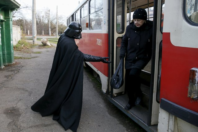 Darth Mykolaiovych Vader, who is dressed as the Star Wars character Darth Vader, poses for a picture as he tries to help a woman exit a tram in Odessa, Ukraine, December 3, 2015. (Photo by Valentyn Ogirenko/Reuters)