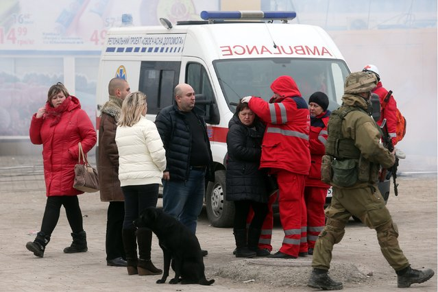Emergency medical workers provide medical care to unjured people after shelling  in the southern Ukrainian port city of Mariupol on 24, 2015. (Photo by AFP Photo/Stringer)
