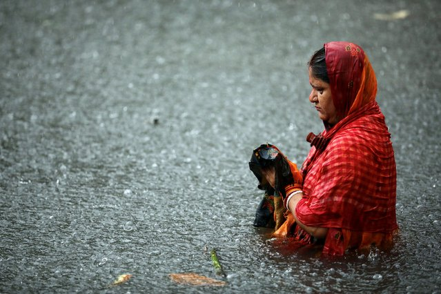 A Hindu devotee stands on the water of the Buriganga river during rain as they observe Chhath Puja in Dhaka, Bangladesh, November 20, 2020. (Photo by Mohammad Ponir Hossain/Reuters)