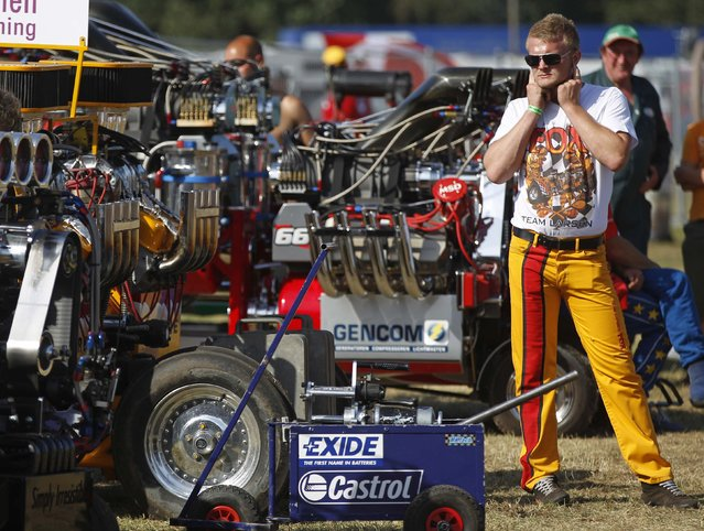 A driver blocks his ears during the Tractor Pulling Euro Championships in the western German town of Fuechtorf September 9, 2012. Eighty teams from across Europe participated in the two-day competition where high-powered tractor prototypes must pull a trailer down a 100-metre (328 ft) track as far as possible. (Photo by Ina Fassbender/Reuters)