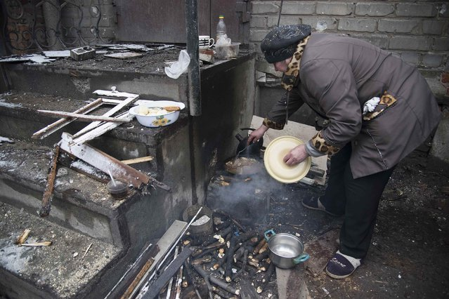 A local resident cooks outside her house in Debaltseve, February 4, 2015. (Photo by Sergey Polezhaka/Reuters)