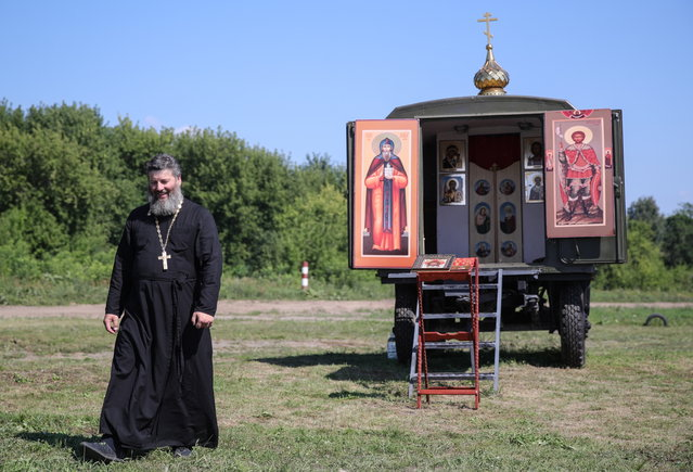 A Russian Orthodox priest near a mobile chapel, during the Open Water contest between pontoon bridge units at the 2018 International Army Games on the Oka River, Vladimir Region, Russia, August 3, 2018. (Photo by Sergei Bobylev/TASS via Getty Images)
