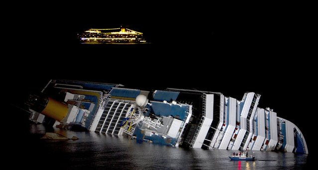 The cruise ship Costa Serena sails as its sister ship Costa Concordia cruise ship lays on its side after it ran aground off the west coast of Italy at Giglio island in this January 18, 2012 file photo. (Photo by Reuters/Stringer)
